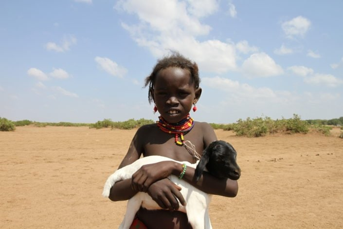 A young Dassanech girl holds her little goat