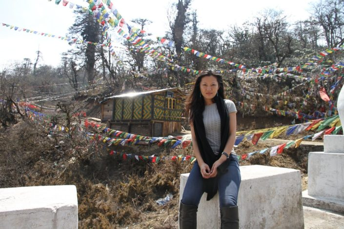 monastery-bhutan-flags-behind-woman