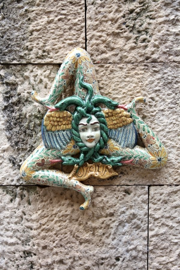 Trinacria. It is the symbol of the Helenic nature of Sicily. It is made up of the head of Medusa whose head is entwined with snakes & was able with a glance to turn men into stone. The head is surrounded by three bent running legs, which represent the three capes of Sicily